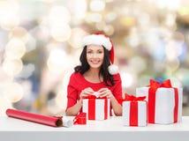 Mujer sonriente en regalos del embalaje del sombrero del ayudante de santa Imagenes de archivo