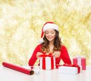 Mujer sonriente en regalos del embalaje del sombrero del ayudante de santa Imagen de archivo