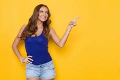 Mujer sonriente en señalar azul de la camisa Imágenes de archivo libres de regalías