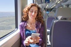 Mujer sonriente en smartphone conmovedor del tren Foto de archivo