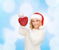 Mujer sonriente en sombrero del ayudante de santa con el corazón rojo Foto de archivo libre de regalías