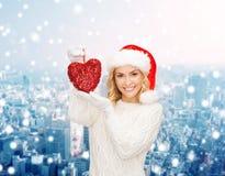 Mujer sonriente en sombrero del ayudante de santa con el corazón rojo Imágenes de archivo libres de regalías