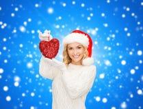Mujer sonriente en sombrero del ayudante de santa con el corazón rojo Fotografía de archivo libre de regalías