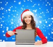 Mujer sonriente en sombrero del ayudante de santa con el ordenador portátil Fotos de archivo