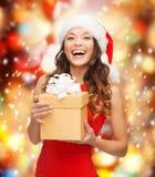 Mujer sonriente en sombrero del ayudante de santa con la caja de regalo Imagen de archivo libre de regalías