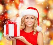 Mujer sonriente en sombrero del ayudante de santa con la caja de regalo Fotografía de archivo libre de regalías