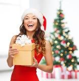 Mujer sonriente en sombrero del ayudante de santa con la caja de regalo Fotos de archivo libres de regalías