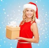 Mujer sonriente en sombrero del ayudante de santa con la caja de regalo Fotografía de archivo