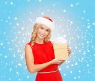 Mujer sonriente en sombrero del ayudante de santa con la caja de regalo Imagen de archivo