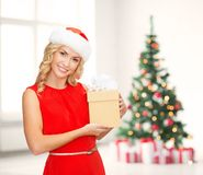 Mujer sonriente en sombrero del ayudante de santa con la caja de regalo Fotos de archivo