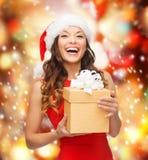 Mujer sonriente en sombrero del ayudante de santa con la caja de regalo Foto de archivo libre de regalías
