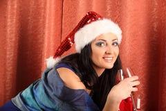 Mujer sonriente en sombrero del ayudante de santa sobre sala de estar con el fondo del árbol de navidad Imagenes de archivo