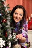 Mujer sonriente en sombrero del ayudante de santa sobre sala de estar con el fondo del árbol de navidad Imagen de archivo