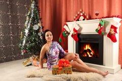 Mujer sonriente en sombrero del ayudante de santa sobre sala de estar con el fondo del árbol de navidad Fotos de archivo libres de regalías