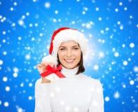Mujer sonriente en sombrero y cascabeles del ayudante de santa Fotografía de archivo libre de regalías