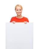 Mujer sonriente en suéter con el tablero blanco en blanco Imagen de archivo