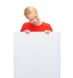 Mujer sonriente en suéter con el tablero blanco en blanco Foto de archivo libre de regalías