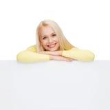 Mujer sonriente en suéter con el tablero blanco en blanco Foto de archivo