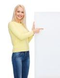 Mujer sonriente en suéter con el tablero blanco en blanco Imagen de archivo libre de regalías