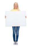 Mujer sonriente en suéter con el tablero blanco en blanco Fotos de archivo libres de regalías