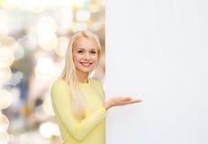 Mujer sonriente en suéter con el tablero blanco en blanco Imagenes de archivo