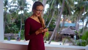 Mujer sonriente en textos de las gafas en el teléfono y negociaciones almacen de metraje de vídeo