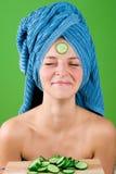 Mujer sonriente en toalla azul y máscara del pepino Imagen de archivo
