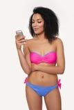 Mujer sonriente en traje de baño con el teléfono celular Foto de archivo