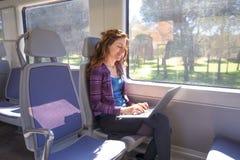Mujer sonriente en tren que mecanografía en el ordenador portátil Fotografía de archivo