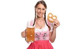 Mujer sonriente en un dirndl con una cerveza y un pretzel Imagen de archivo libre de regalías