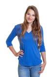 Mujer sonriente en una camisa azul y vaqueros Imagenes de archivo
