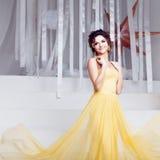 Mujer sonriente en vestido de noche amarillo y con Fotografía de archivo libre de regalías