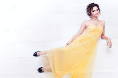 Mujer sonriente en vestido de noche amarillo y con el peinado hermoso, partido Fotos de archivo