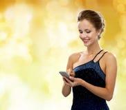 Mujer sonriente en vestido de noche con smartphone Imágenes de archivo libres de regalías