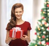 Mujer sonriente en vestido rojo con la caja de regalo Foto de archivo libre de regalías