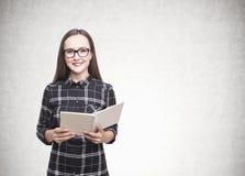 Mujer sonriente en vidrios, cuaderno, concreto Imagenes de archivo