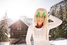 Mujer sonriente en vidrios divertidos de una Navidad cerca de una casa de la montaña Fotos de archivo
