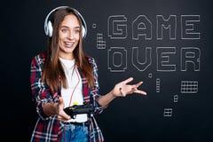 Mujer sonriente encantada de Yong que juega a los videojuegos Foto de archivo libre de regalías