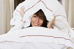 Mujer sonriente entre las almohadillas Imagen de archivo libre de regalías