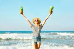 Mujer sonriente feliz con dos piñas en un verano soleado Foto de archivo