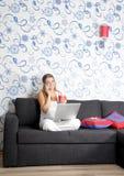 Mujer sonriente feliz con el funcionamiento de la computadora portátil Imagen de archivo libre de regalías