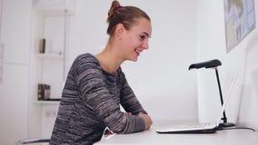 Mujer sonriente feliz con el ordenador portátil que tiene videoconferencia en casa u oficina Ella está agitando su mano almacen de video