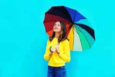 Mujer sonriente feliz con el paraguas colorido en el día del otoño que mira para arriba sobre fondo azul colorido Fotos de archivo libres de regalías