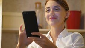 Mujer sonriente feliz con el smartphone, ascendente cercano del retrato almacen de video