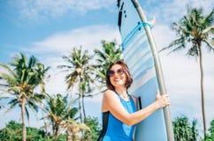 Mujer sonriente feliz con el tablero de resaca que presenta en la playa tropical Fotografía de archivo