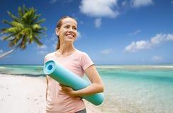 Mujer sonriente feliz con la estera del ejercicio sobre la playa fotografía de archivo libre de regalías