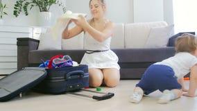 Mujer sonriente feliz con la maleta adorable del embalaje del bebé por vacaciones de verano metrajes
