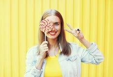 Mujer sonriente feliz con la piruleta dulce del caramelo sobre fondo amarillo colorido Fotos de archivo libres de regalías