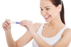 Mujer sonriente feliz con la prueba de embarazo. Foto de archivo