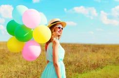Mujer sonriente feliz con los globos coloridos de un aire que disfruta de un día de verano en el cielo azul del prado Fotos de archivo